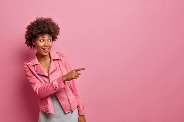Heureuse jeune femme bouclée à la peau sombre indique à distance voit quelque chose d'étonnant rire positivement