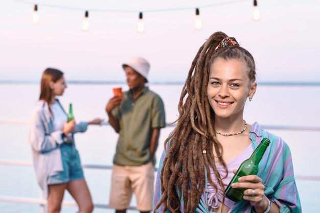 Heureuse jeune femme avec une bouteille de bière debout contre un couple interculturel