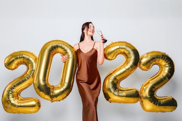 Heureuse jeune femme brune avec une coupe de champagne près de ballons dorés sur fond blanc nouvel oui...