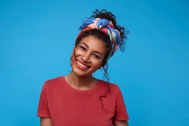 Heureuse jeune femme brune mignonne bouclée avec piercing nez montrant ses émotions agréables et souriant joyeusement tout en regardant à l'avant, isolé sur mur bleu