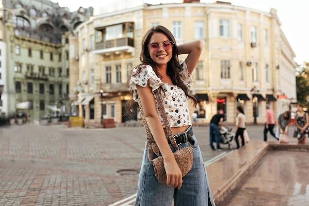 Heureuse jeune femme brune en pantalon en jean élégant et ample et haut fleuri recadrée sourit largement