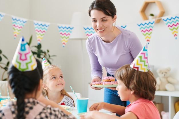 Heureuse jeune femme brune se penchant sur la table d'anniversaire servi et offrant des beignets aux petits enfants
