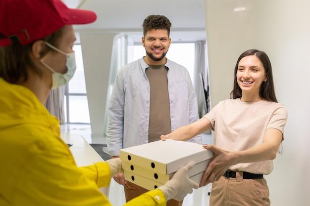 Heureuse jeune femme brune en tenue décontractée regardant avec un sourire à pleines dents un courrier masculin passant sa pile de boîtes avec une pizza commandée