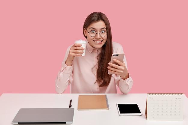 Heureuse jeune femme brune tient un téléphone portable moderne, types des messages texte, porte du café à emporter à la main, utilise le bloc-notes pour enregistrer des informations