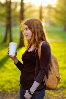 Heureuse jeune femme buvant du café ou du thé en plein air