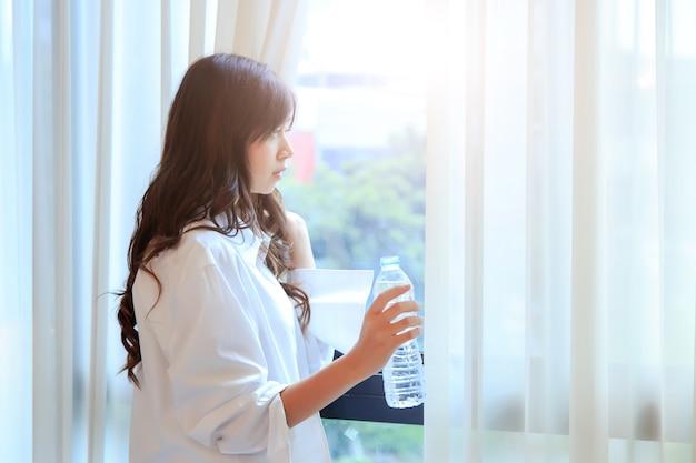 Heureuse jeune femme buvant de l'eau pure dans sa chambre. concept pour la santé.