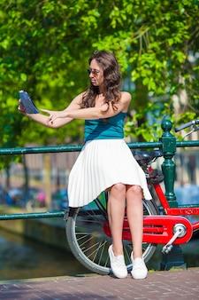 Heureuse jeune femme avec une carte de la ville souriante à vélo