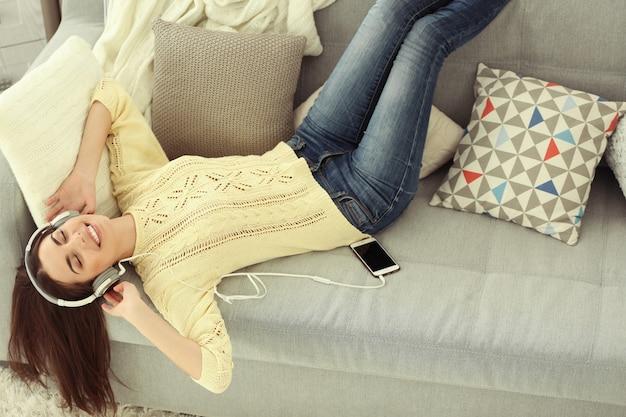 Heureuse jeune femme avec un casque d'écoute de la musique sur un canapé à la maison