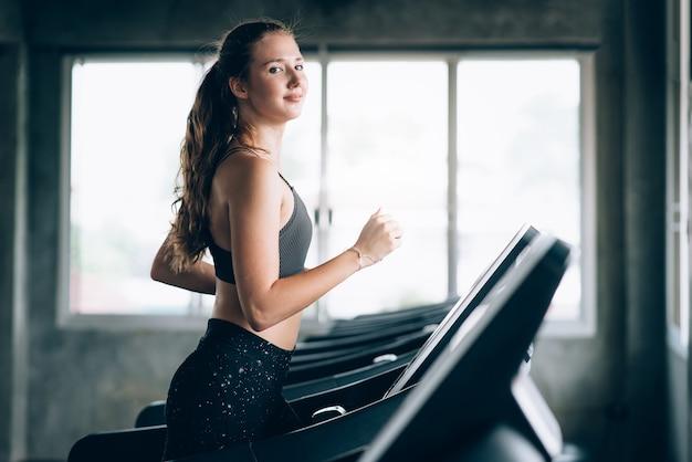 Heureuse jeune femme caucasienne faire cardio par course sur tapis roulant dans la salle de gym