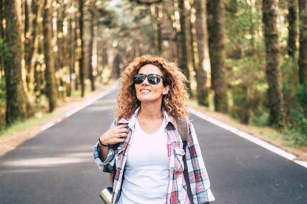 Heureuse jeune femme caucasienne marchant et voyageant sur une route avec forêt