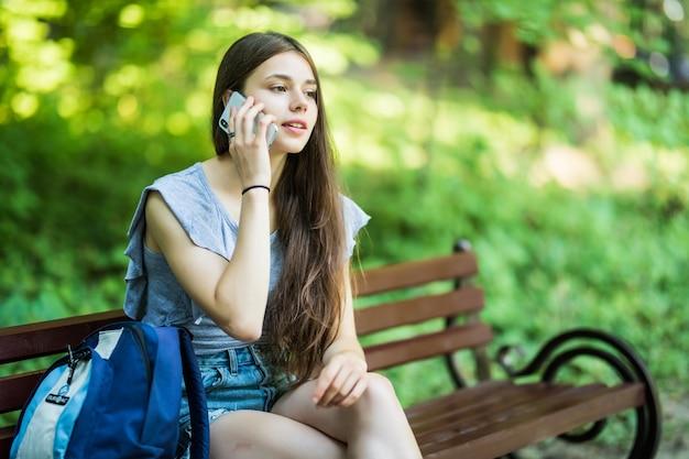 Heureuse jeune femme caucasienne mignonne sourit et parle au téléphone dans le parc