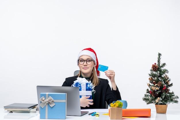 Heureuse jeune femme avec chapeau de père noël et portant des lunettes assis à une table tenant un cadeau de noël et une carte bancaire sur fond blanc