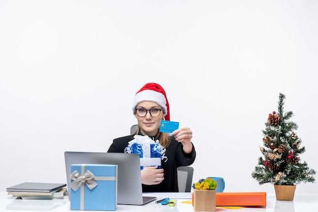 Heureuse jeune femme avec chapeau de père noël et portant des lunettes assis à une table tenant un cadeau de noël et montrant une carte bancaire sur fond blanc