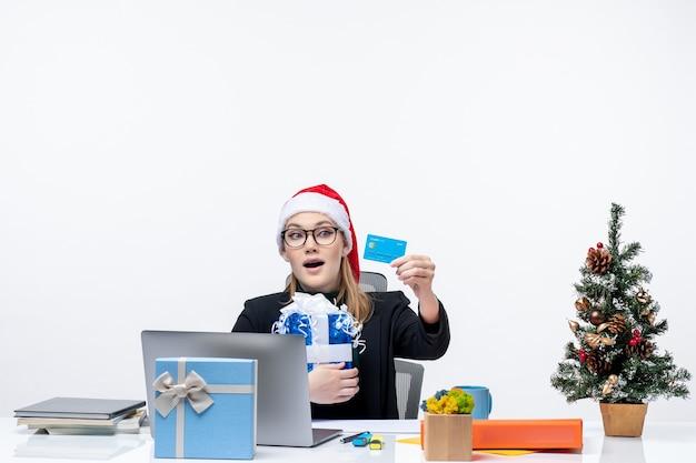 Heureuse jeune femme avec chapeau de père noël et portant des lunettes assis à une table tenant un cadeau de noël et regardant la carte bancaire sur fond blanc