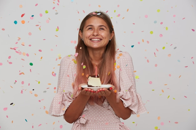 Heureuse jeune femme charmante aux cheveux longs brun clair à la joyeusement de côté tout en gardant le gâteau d'anniversaire dans ses mains, faisant le souhait et se réjouissant de la belle fête, isolée sur mur blanc
