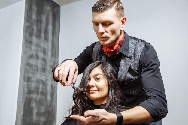 Heureuse jeune femme et coiffeur coupe les pointes des cheveux au salon.