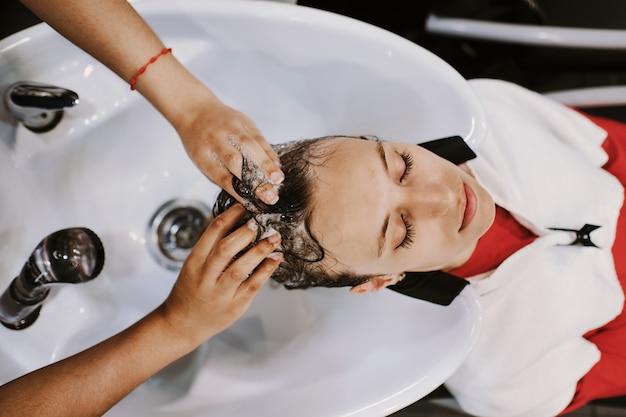 Heureuse jeune femme avec coiffeur laver la tête au salon de coiffure