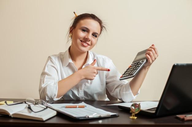 Heureuse jeune femme comptable avec calculatrice