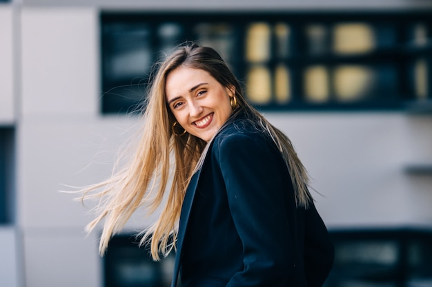 Heureuse jeune femme en costume noir sourit