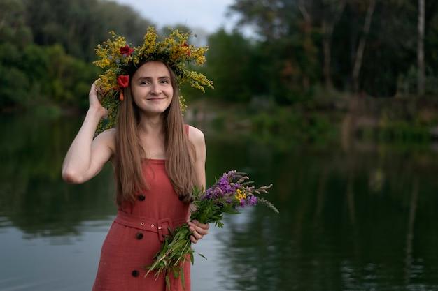 Heureuse jeune femme avec une couronne sur la tête avec bouquet de fleurs sauvages