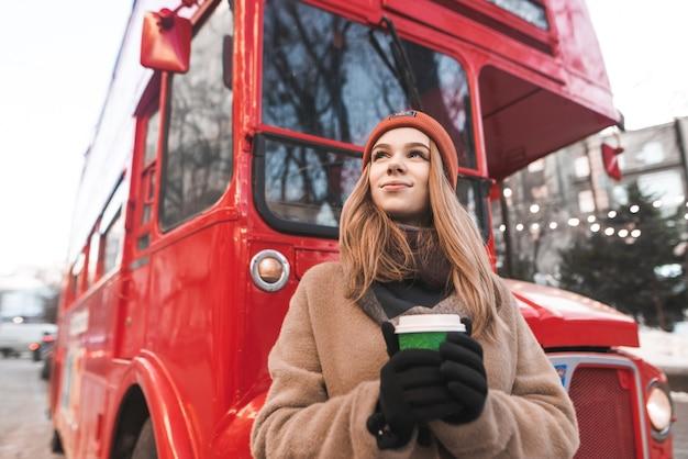 Heureuse jeune femme dans une casquette et des vêtements chauds debout dans la rue, tenant une tasse de café dans ses mains, regardant de côté et souriant