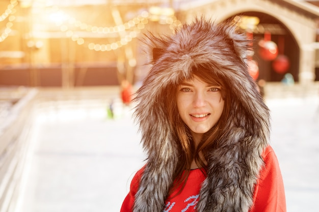 Heureuse jeune femme dans un chapeau de loup en hiver à la patinoire pose dans un chandail rouge à l'extérieur dans l'après-midi