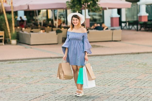 Heureuse jeune femme dans un chapeau et une robe détient des sacs à provisions dans ses mains et sourit dans une ville d'été