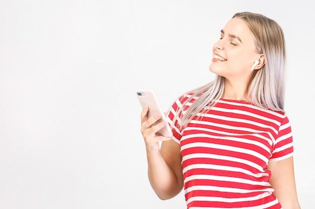 Heureuse jeune femme dans les écouteurs écoute de la musique avec un téléphone intelligent, danse, s'amuse et sourit. fond blanc, isolé.