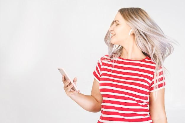 Heureuse jeune femme dans les écouteurs écoute de la musique avec un téléphone intelligent