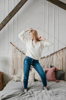 Heureuse jeune femme dans les écouteurs, écouter de la musique à partir de smartphone et danser sur le lit à la maison