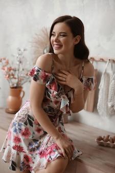 Heureuse jeune femme dans une robe courte avec imprimé fleuri posant à l'intérieur de la cuisine le matin