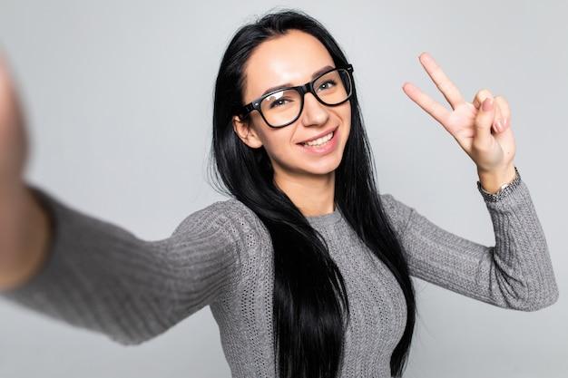Heureuse jeune femme dans des verres avec un sourire rayonnant faisant selfie avec v-signe isolé sur mur gris