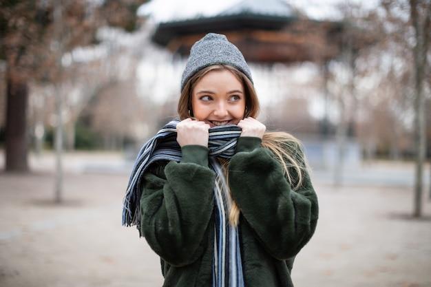 Heureuse jeune femme dans des vêtements chauds enveloppant dans une écharpe et regardant au loin dans un parc en automne par une journée très froide