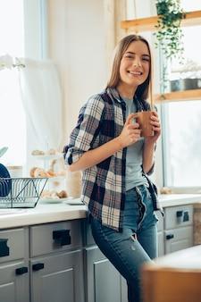 Heureuse jeune femme debout dans la cuisine avec une tasse de thé et l'air détendue