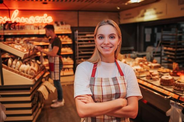 Heureuse jeune femme debout dans l'épicerie.