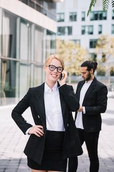 Heureuse jeune femme debout devant son collègue parlant au téléphone