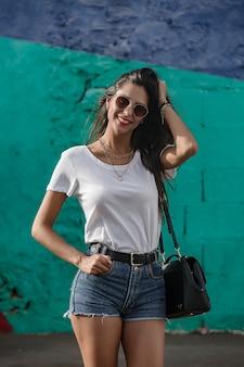 Heureuse jeune femme debout à l'extérieur et souriant