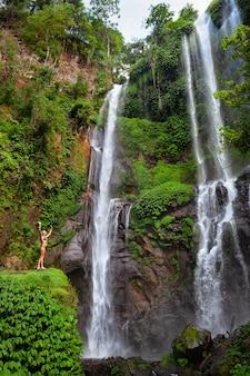 Heureuse jeune femme debout sous la cascade de sekumpul, voir sur l'eau qui tombe.