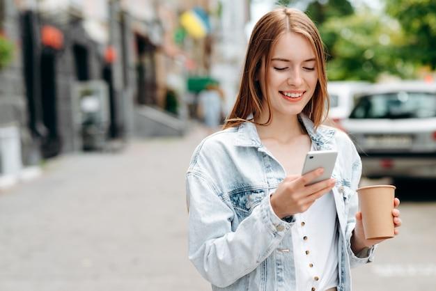 Heureuse jeune femme debout et tenant un smartphone en regardant l'écran en plein air