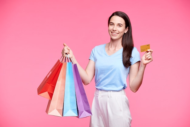 Heureuse jeune femme décontractée avec des sacs en papier et une carte de crédit en plastique se vantant de ses achats dans l'isolement