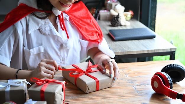 Heureuse jeune femme décorant un cadeau de noël avec un ruban rouge.