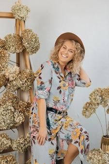 Heureuse jeune femme décoratrice au chapeau, debout et souriante rayonnante de bonheur. concept de travail réussi et de faire ce que vous aimez.