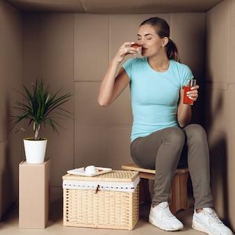 Heureuse jeune femme déjeune dans une boîte en carton.