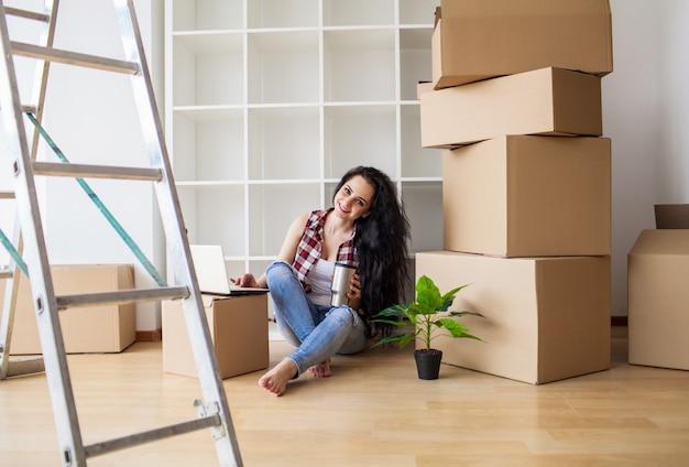 Heureuse jeune femme déménageant dans une nouvelle maison