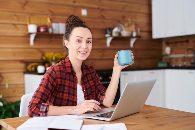 Heureuse jeune femme designer ou pigiste avec une tasse de thé ou de café à la recherche de nouvelles idées dans la cuisine sur des sites web