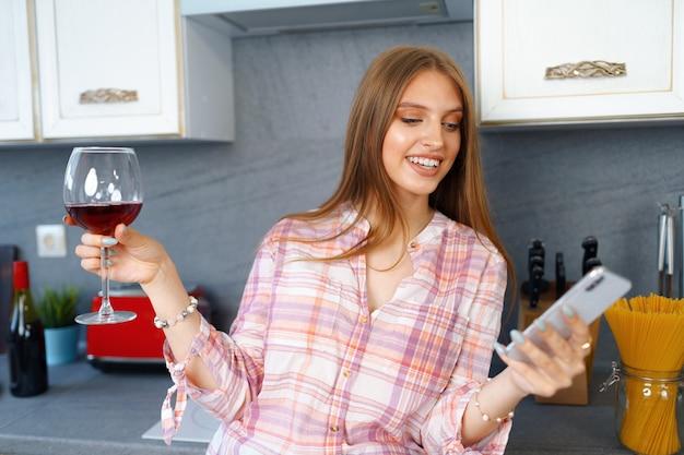 Heureuse jeune femme détendue debout dans la cuisine avec un verre de vin rouge et à l'aide de son smartphone pour un appel vidéo