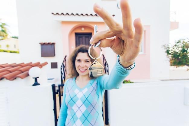 Heureuse jeune femme devant la nouvelle maison avec les nouvelles clés de la maison