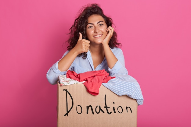 Heureuse jeune femme avec don de vêtements debout sur rose, portant une tenue décontractée, garde une main sous le menton