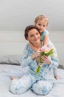 Heureuse jeune femme donnant une promenade en ferroutage à sa petite fille sur le lit, tenant un bouquet de fleurs de tulipes