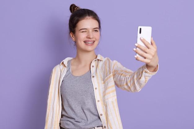 Heureuse jeune femme drôle posant isolé sur mur lilas